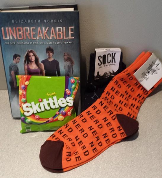 Secret Santa Gift from Eileen: Unbreakable by Elizabeth Norris, Sour Skittles, and nerd socks