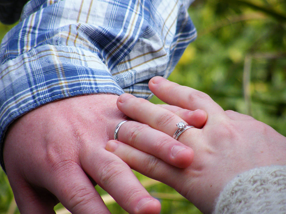 A close up of our wedding rings and us linking fingers