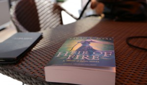Reading Heir of Fire by the pool