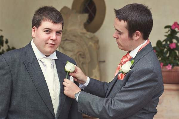 The best man helping the groom get ready
