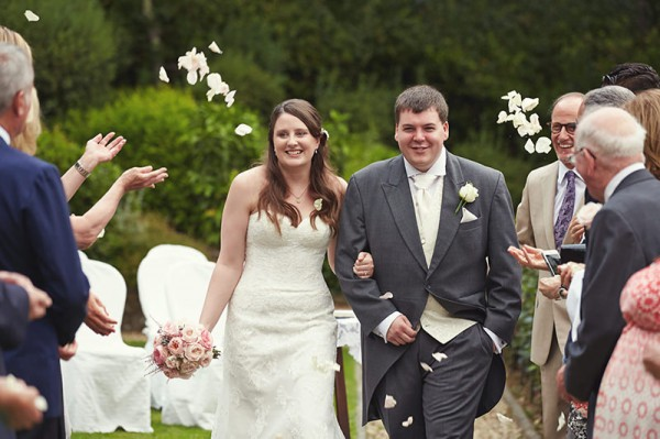 People throwing flowers petals at the bride and groom