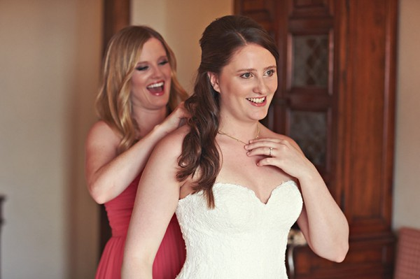A bridesmaid putting a necklace on the bride