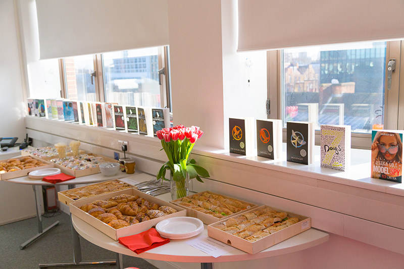 Books and food on a table by the window