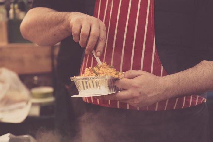 A chef preparing a bowl of paella