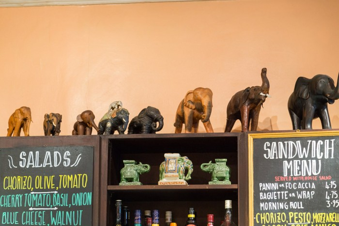 Elephant sculptures and decorations on a shelf in The Elephant House