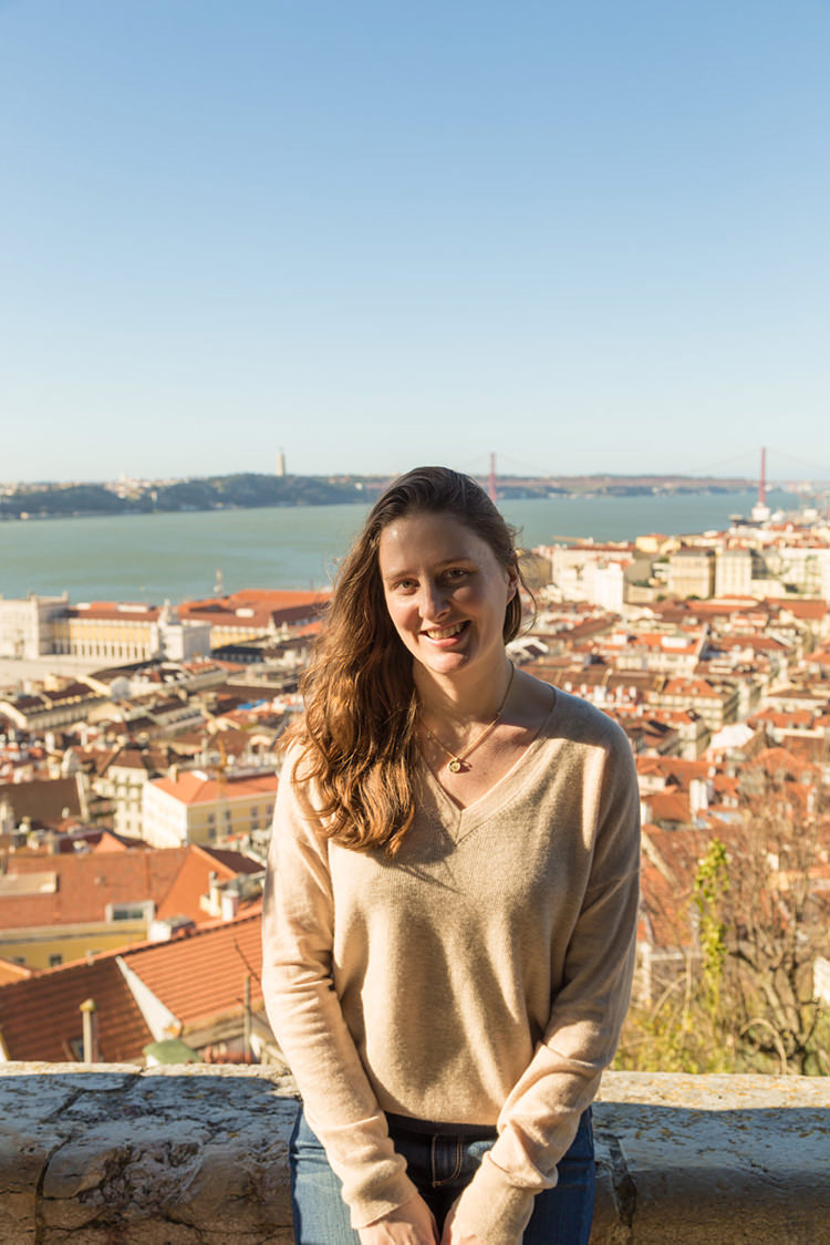 Me sitting on the edge of a wall, overlooking the city of Lisbon
