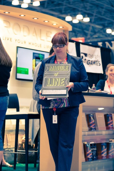 "A Macmillan employee holding a sign saying ""Middle of Line"""