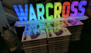 Warcross ARCs in front of glowing sign