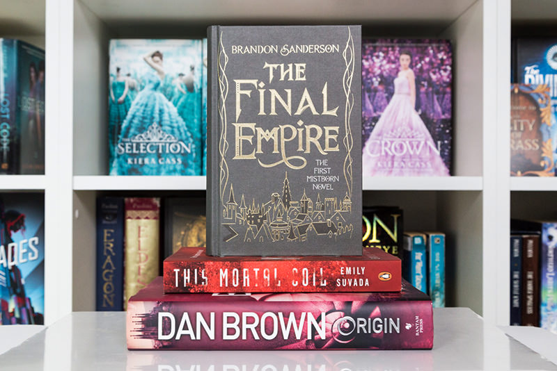 Stack of books in front of bookshelves: The Final Empire, This Mortal Coil, and Origin